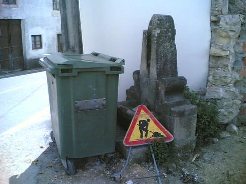 Fonte com caixote do lixo e material de obras