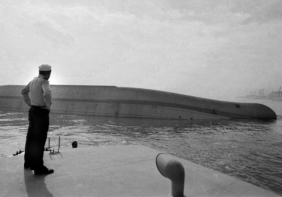 Marinheiro observa os destroços do navio MV Tolla