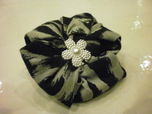 Pregadeira em tecido com padrão preto e bege e flor no centro.