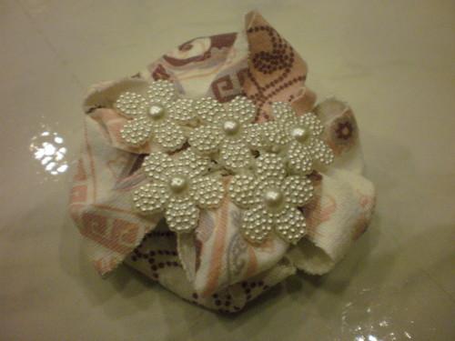 Pregadeira de tecido em tons de rosa e branco e flores brancas no centro.